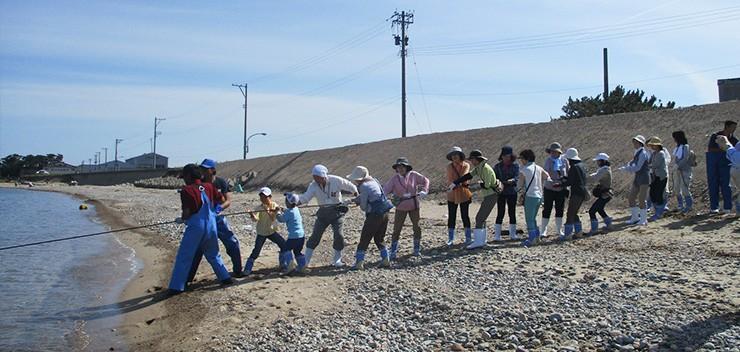 みんなで力を合わせて地引網を引きます。