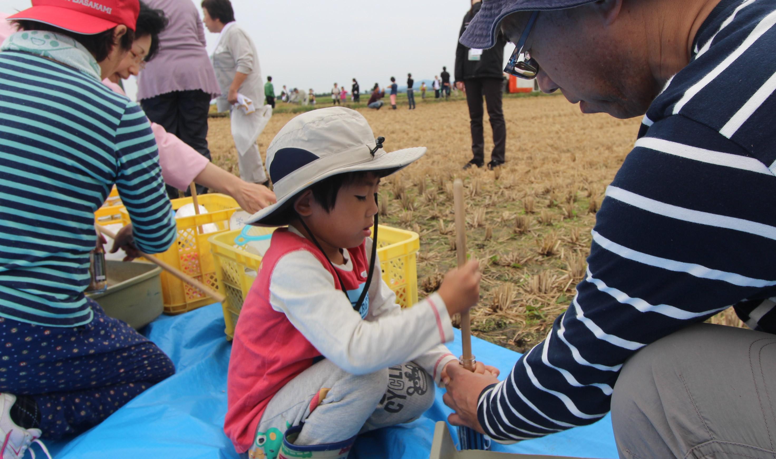 刈り取り後は、稲が白米になる過程を学ぶ「お米のべんきょう」。びんに入れた米を棒でついて精米する昔ながらのやり方も体験!