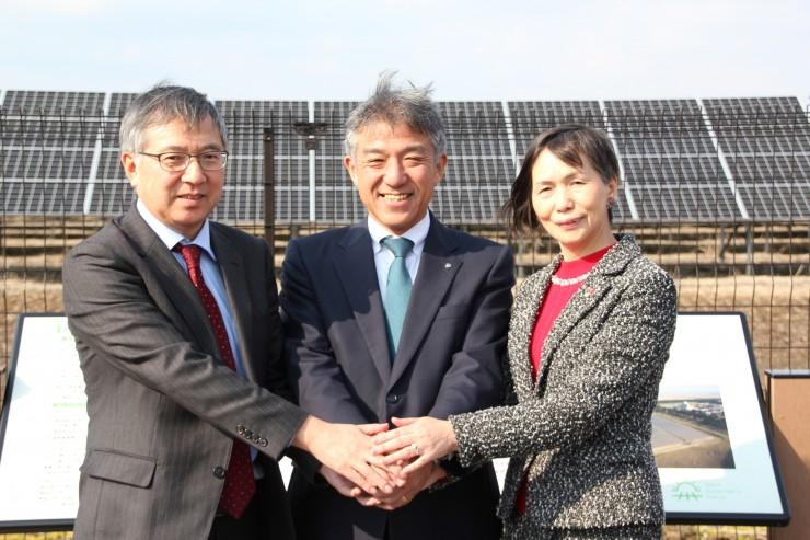 今後もつながりを深めます(発電設備を背に左から原専務理事、高橋大潟村村長、白川副理事長)