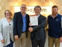 来訪したミルズ社長(中央左)ら訪日団と表彰状を受け取る石田理事長(同右)